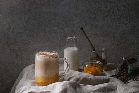 Glass of pumpkin layered spice latte with pumpkin puree, milk foam and cinnamon standing with ingredients in jars and decorative white pumpkins on crumpled table cloth with grey wall at background. Фото со стока