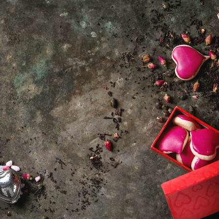 Love Valentines day greeting card with variety of dry tea, rose buds, heart shape homemade almond cookies as gift  and red box over old dark metal background. Top view, space. Square image
