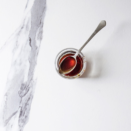 Homemade liquid transparent brown sugar caramel in glass jar with vintage spoon over white marble background. Flat lay, space. Square image Stockfoto
