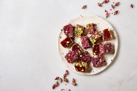 Variedad de postre turco tradicional Delicia turca de diferentes sabores y colores con pétalos de rosa y pistachos en placa de cerámica sobre fondo de mármol blanco. Endecha plana, espacio