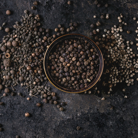 Variety of different black peppers allspice, pimento, monks pepper, peppercorns and ground powder in tin can over old black iron texture background. Top view, space. Square image Standard-Bild - 113381196