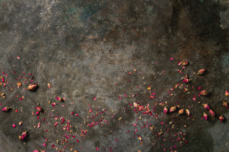 Old dark metal background with dry pink rose buds and petals. Copy space.