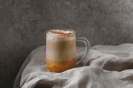 Glass of pumpkin layered spice latte with pumpkin puree, milk foam and cinnamon standing on crumpled table cloth with grey wall at background. Copy space