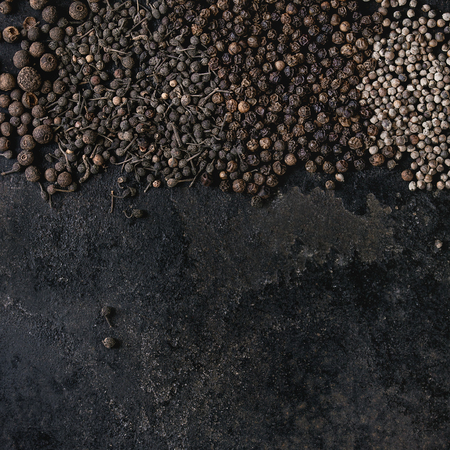 Variety of different black peppers allspice, pimento, monks pepper, peppercorns over old black iron texture surface. Food background. Top view, space. Square image Banque d'images