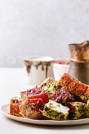 Variedad de postre turco tradicional Delicia turca de diferentes gustos y colores pétalos de rosa y pistachos en placa de cerámica con jezve de café y jarra de leche en la mesa de mármol blanco. De cerca