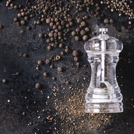 Variety of different black peppers allspice, pimento, long pepper, monks pepper, peppercorns and ground powder from pepper mill over old black iron texture background. Top view. Square image