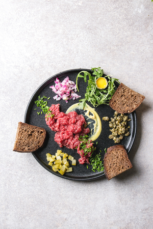 Beef tartare with quail egg in shell, bread, cutting pickled cucumbers, capers, red onion, chives, arugula salad served in black ceramic plate over grey background. Flat lay, space