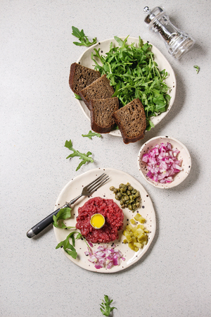 Beef tartare with quail egg in shell, bread, cutting pickled cucumbers, capers, red onion, arugula salad served in spotted ceramic plates with pepper mill on grey background. Flat lay, space Stock Photo