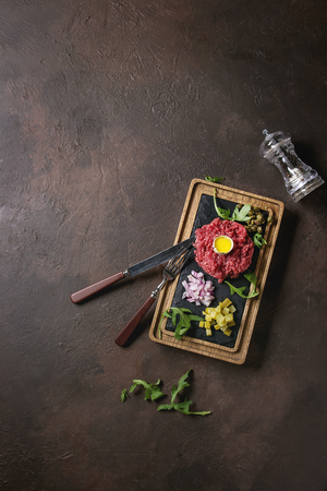 Beef tartare with quail egg in shell, cutting pickled cucumbers, capers, red onion, chives, arugula served on wooden black slate board with cutlery on dark texture background. Flat lay, space Stock Photo
