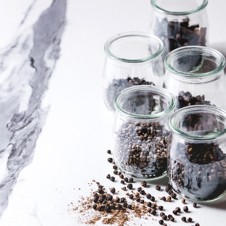 Variety of different black peppers allspice, pimento, long pepper, monks pepper, peppercorns and ground powder in glass jars on white marble kitchen table. Square image Standard-Bild - 113381732