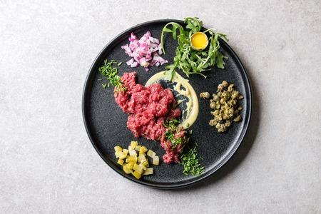 Beef tartare with quail egg in shell, cutting pickled cucumbers, capers, red onion, chives, arugula salad served in black ceramic plate over grey background. Flat lay, space
