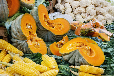 Turkish farmer market. Heap of fresh organic vegetables on the counter cauliflower, corn cobs, greens, sliced pumpkins.