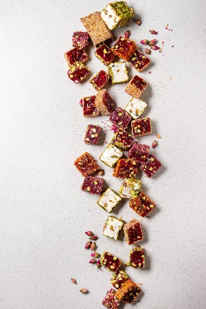 Variety of traditional turkish dessert Turkish Delight different taste and colors with rose petals and pistachio nuts over grey spotted background. Flat lay, copy copy space