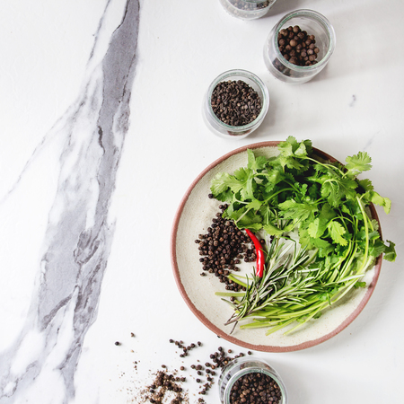 Variety of different black peppers allspice, pimento, long pepper, monks pepper, peppercorns in glass jars, pepper and fresh herbs in plate over white marble background. Top view, space. Square image Standard-Bild - 113381970