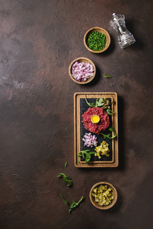 Beef tartare with quail egg in shell, cutting pickled cucumbers, capers, red onion, chives, arugula served on wooden black slate board with pepper mill on dark texture background. Flat lay, space Stock Photo