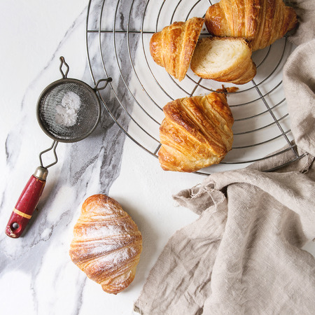 Homemade croissant whole and sliced with sugar powder on cooling rack with linen cloth over white marble background. Flat lay, space. Square image Stock Photo