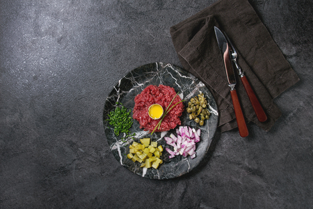 Beef tartare with quail egg in shell, cutting pickled cucumbers, capers, red onion, chives served in marble plates with cutlery and cloth napkin on black texture background. Flat lay, space Stock Photo - 113382137