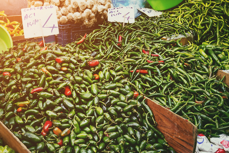 Turkish farmer market. Heap of fresh organic vegetables on the counter varyety of green hot peppers.