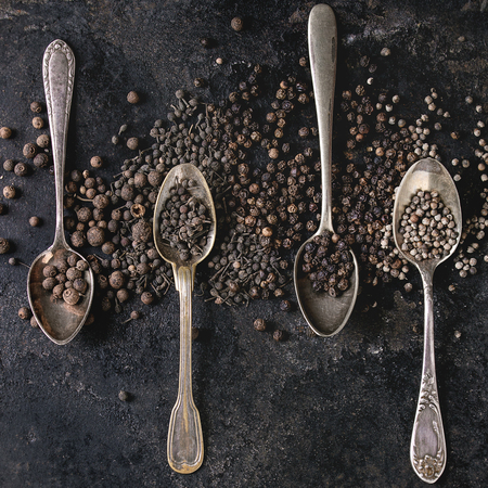Variety of different black peppers allspice, pimento, monks pepper, peppercorns in vintage spoons over old black iron texture background. Top view, space. Square image Standard-Bild - 113382157