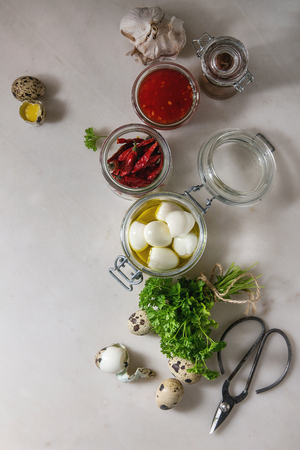 Ingredients for homemade pickled marinated quail eggs. Boiled eggs in olive oil, tomato sauce, chili peppers in jars, fresh parsley, scissors over white marble background. Flat lay, space Stock Photo