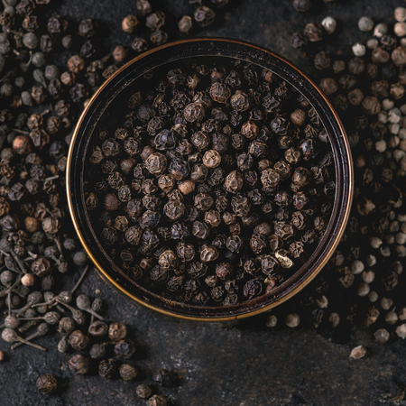 Variety of different black peppers allspice, pimento, monks pepper, peppercorns in tin can over old black iron texture background. Top view, space. Close up. Square image