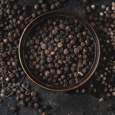 Vielzahl verschiedener schwarzer Pfeffer Piment, Piment, Mönchspfeffer, Pfefferkörner in Blechdose über altem schwarzem Eisenstrukturhintergrund. Ansicht von oben, Raum. Nahansicht. Quadratisches Bild