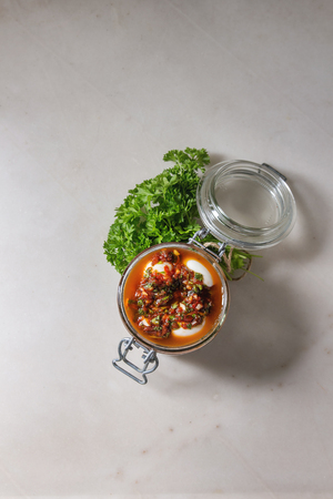 Opened Jar with homemade pickled marinated quail eggs in tomato and olive oil sauce with anchovies and fresh parsley on white marble background. Flat lay, space Stock Photo - 113382250