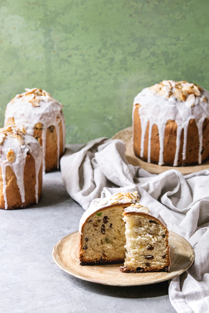 Set of traditional Russian and Ukrainian Easter cake Kulich Paska bread glazed with almond, whole and sliced, served on ceramic plate with cloth over grey table with green wall as background. Stock Photo