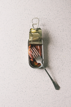 Pickled salted anchovies fillet in oil in open tin can with fork over grey spotted background. Flat lay, copy space