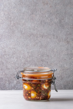 Jar with homemade pickled marinated quail eggs in tomato and olive oil sauce with anchovies and fresh parsley on white marble kitchen table. Copy space
