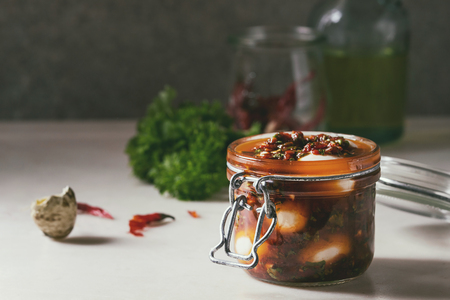 Opened Jar with homemade pickled marinated quail eggs in tomato and olive oil sauce with anchovies and fresh parsley on white marble kitchen table. Ingredients above.