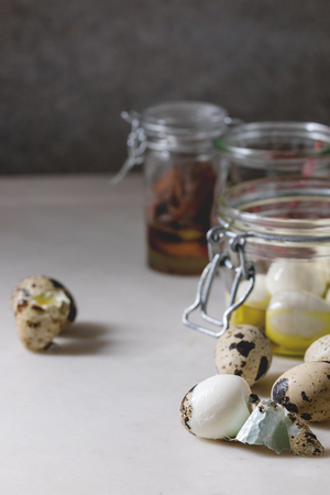 Ingredients for homemade pickled marinated quail eggs. Boiled eggs with olive oil in jar on white marble kitchen table. Close up Stock Photo