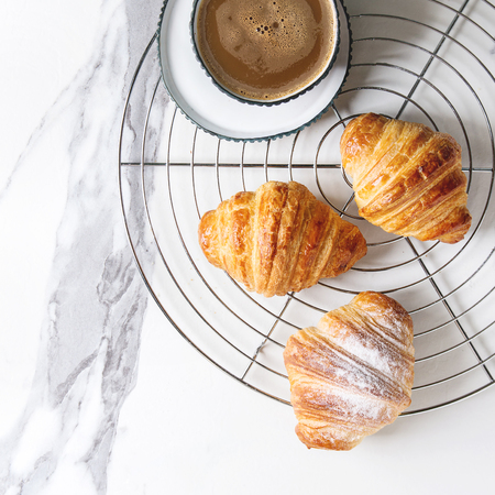 Homemade croissant with sugar powder on cooling rack with cup of coffee over white marble background. Flat lay, space. Square image Stock Photo