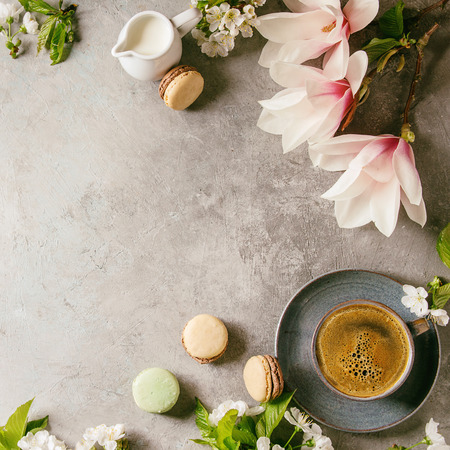 Blue cup of black espresso coffee french dessert macaroons, cream and spring flowers magnolia, blooming cherry branches over grey texture background. Top view, space. Square image
