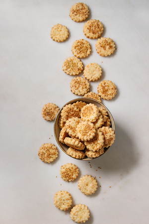 Homemade snack shortbread cheese sesame cookies in bowl over white marble background. Flat lay, space 写真素材