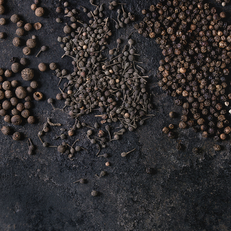 Variety of different black peppers allspice, pimento, monks pepper, peppercorns over old black iron texture surface. Food background. Top view, space. Square image Standard-Bild - 115312713