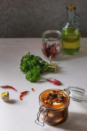 Opened Jar with homemade pickled marinated quail eggs in tomato and olive oil sauce with anchovies and fresh parsley on white marble kitchen table. Ingredients above. Stock Photo - 115312977