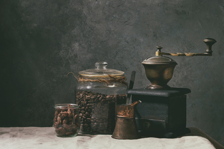 Coffee collection. Roasted black coffee beans in jar, vintage coffee grinder, jezve pot, sweet sugared almond standing on table with linen table cloth.