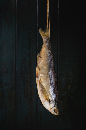 Dried fish or stockfish on thread over dark wooden background