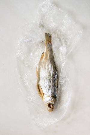 Dried fish or stockfish on plastic bag over white marble background. Flat lay, space