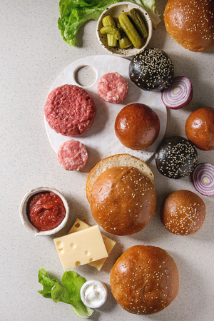 Ingredients for cooking homemade hamburgers. Meat beef burger, cheese, ketchup sauce, tomato, black and white buns, salad, pickled cucumbers over grey background. Top view with space.