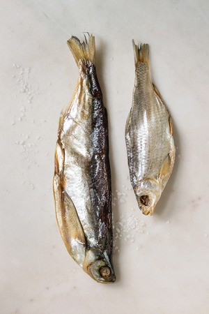 Dried fish or stockfish over white marble background. Flat lay, space Stockfoto