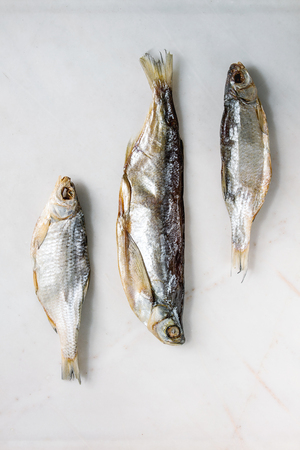 Dried fish or stockfish over white marble background. Flat lay, space Banque d'images