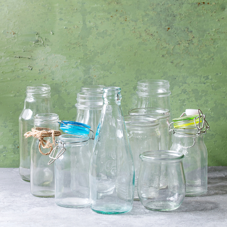 Variety of different shape empty opened glass bottles with and without lids standing on grey table with green wall as background. Square image Archivio Fotografico - 115316588