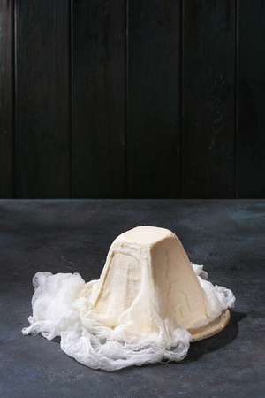 Traditional Russian Easter cottage cheese dessert, Orthodox Paskha cheesecloth standing in ceramic plate on dark texture table. Copy space Фото со стока