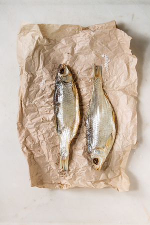 Dried fish or stockfish on crumpled paper over white marble background. Flat lay, space