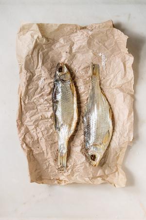 Gedroogde vis of stokvis op verfrommeld papier over witte marmeren achtergrond. Platliggend, ruimte