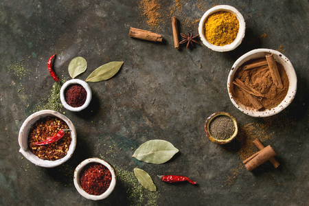 Spices seasoning and herbs variety in ceramic bowls. Different ground peppers, chili pepper, turmeric, bay leaf, cinnamon over dark metal background. Flat lay, space. Cooking concept Stock Photo