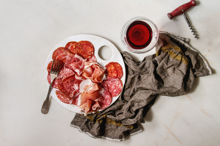 Antipasto meat platter assorti of sliced jamon, salami, chorizo sausage on white ceramic board with glass of red wine on cloth over white marble background. Flat lay, space