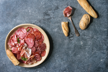Antipasto meat platter assorti of sliced jamon, salami, chorizo sausage in ceramic plate with bread over blue texture background. Flat lay, space Banco de Imagens